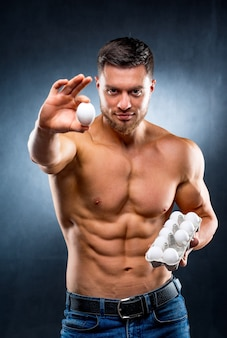 Handsome young sportsman is holding a packaging with eggs