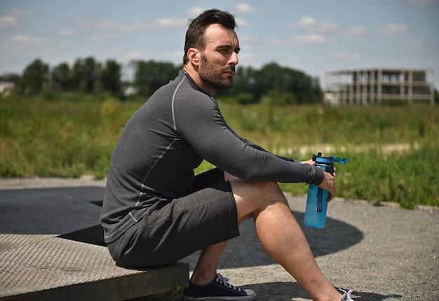 잘생긴 젊은 스포츠맨은 무거운 훈련 후 쉬고, 물병을 들고 옆을 바라보고 있습니다.