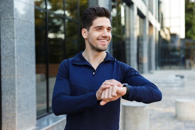 Красивый молодой спортсмен, стоя на открытом воздухе, проверяя время