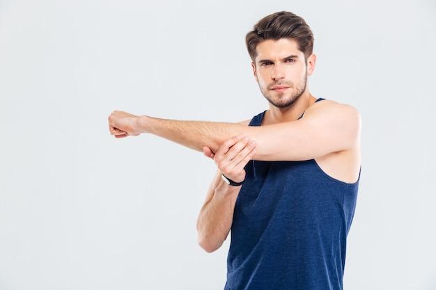 Красивый молодой спортсмен, протягивая руки во время тренировки, изолированные на сером фоне