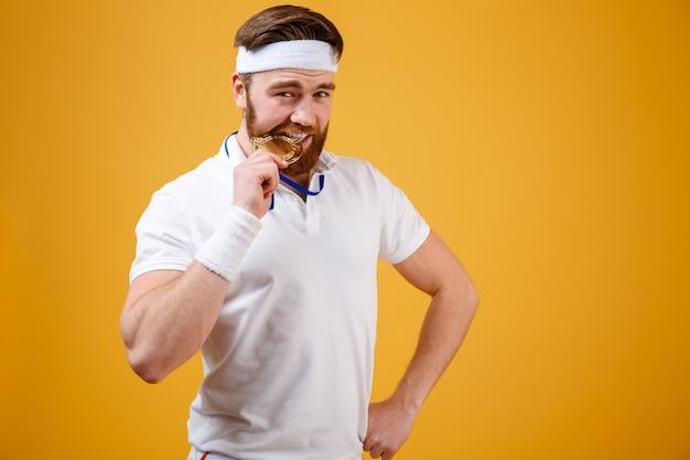 分離されたメダル立っているとハンサムな若いスポーツマン