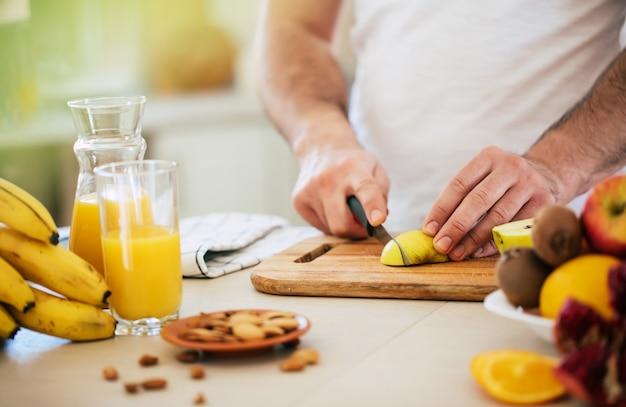 Красивый молодой спортивный улыбающийся мужчина на кухне измельчает фрукты