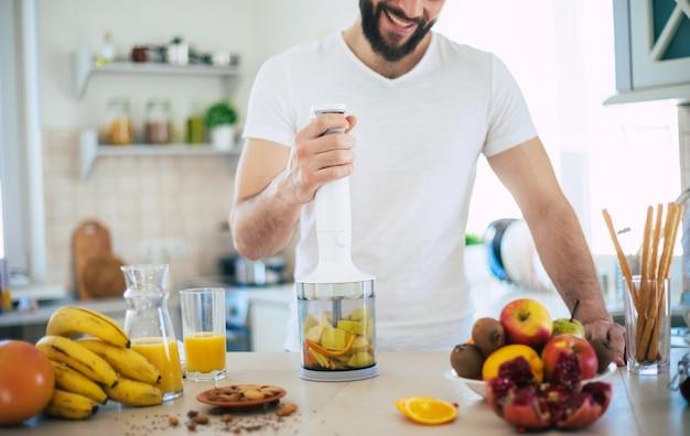 Красивый молодой спортивный улыбающийся мужчина на кухне готовит смузи