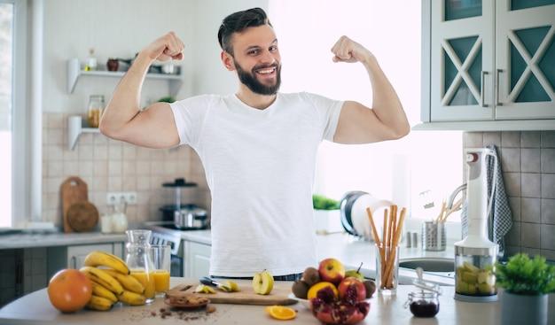 Красивый молодой спортивный улыбающийся человек на кухне с фруктами. концепция здорового питания