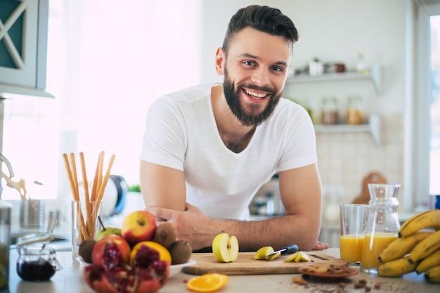 Красивый молодой спортивный улыбающийся человек на кухне