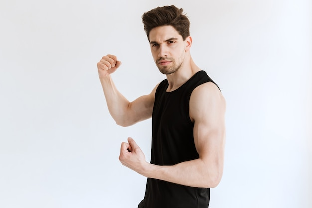 Handsome young strong sports man posing and showing biceps.