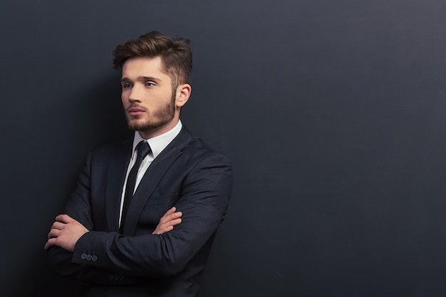 Handsome young student in classic suit is looking away. copyspace background