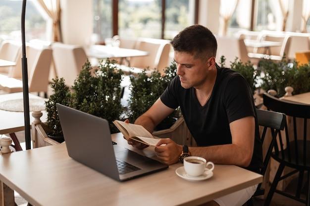 トレンディな黒のtシャツを着たハンサムな若い学生男性が、カフェに座ってコーヒーを飲みながらノートパソコンを読んでいます。