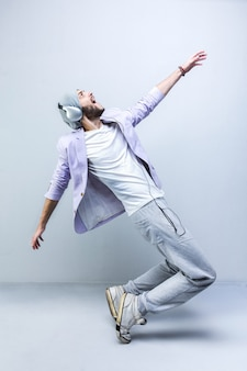 Handsome young stylish man in headphones dancing