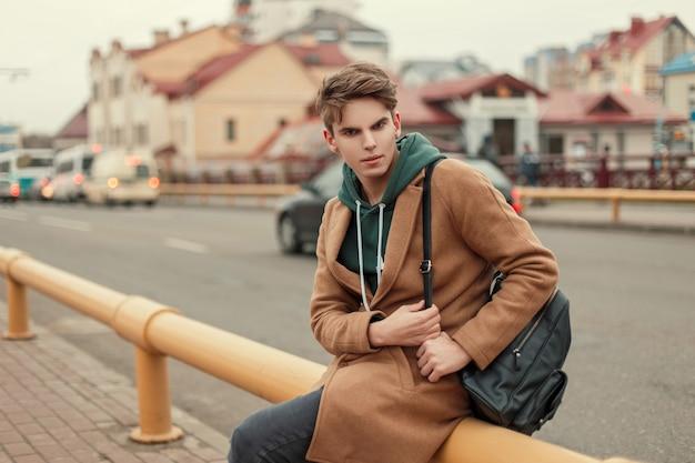 거리에 앉아 세련된 가방과 까마귀와 트렌디 한 코트에 잘 생긴 젊은 세련된 남자