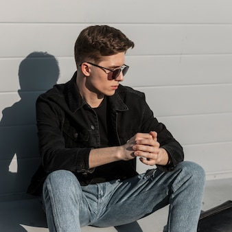 ファッショナブルなジーンズの服にヴィンテージの黒いサングラスをかけたハンサムな若いスタイリッシュな男