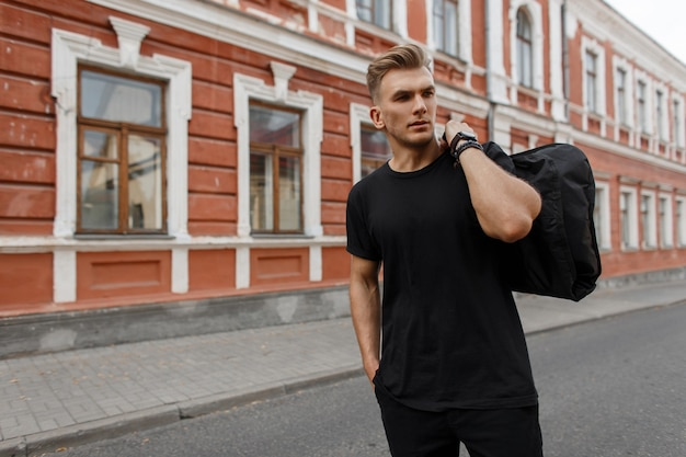 Handsome young stylish model man with hairstyle in black t-shirt with black bag on his shoulder walks on the street