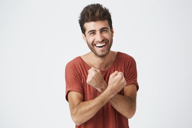 Красивый молодой загорелый мужчина чувствует возбуждение, активно жестикулирует, держит кулаки сжатыми и скрещенными, радостно смеясь, довольный удачей. студент взволнован успешной сдачей экзаменов