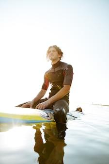 바다에서 서핑 보드에 앉아 수영복에 잘 생긴 젊은 서퍼 남자
