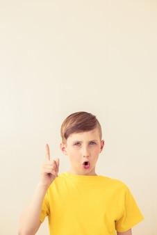 ハンサムな若い十代の少年は彼の指を現しています。コピースペース