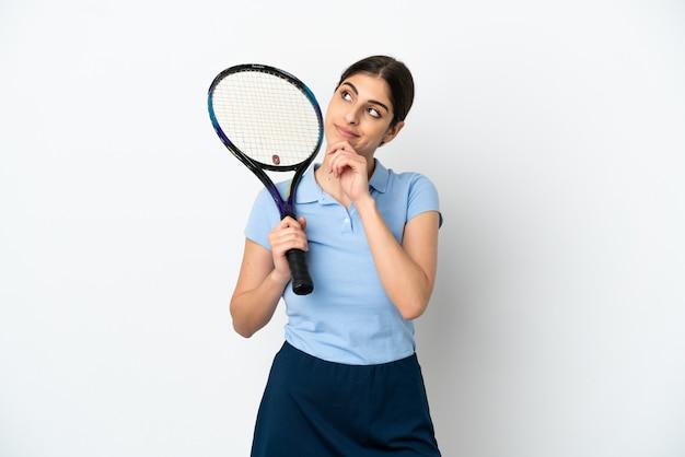 Кавказская женщина красивый молодой теннисист, изолированные на белом фоне и глядя вверх
