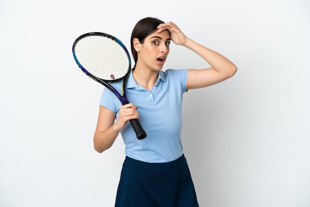 横を見ながら驚きのジェスチャーをしている白い背景で隔離のハンサムな若いテニスプレーヤー白人女性