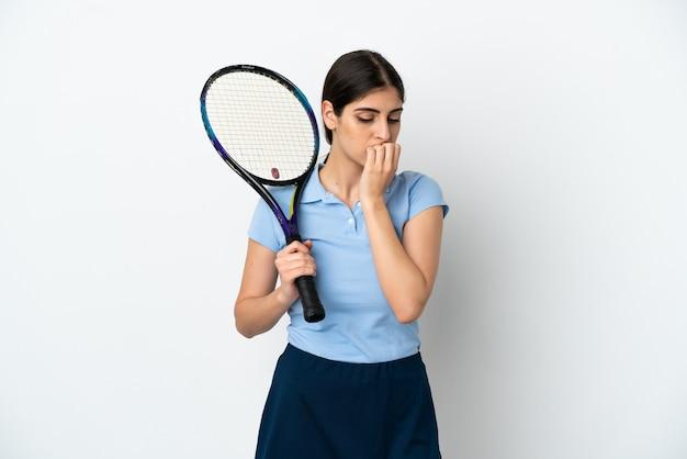 疑いを持っている白い背景で隔離のハンサムな若いテニスプレーヤー白人女性
