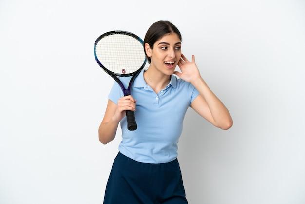 耳に手を置くことによって何かを聞いて白い背景で隔離のハンサムな若いテニスプレーヤー白人女性