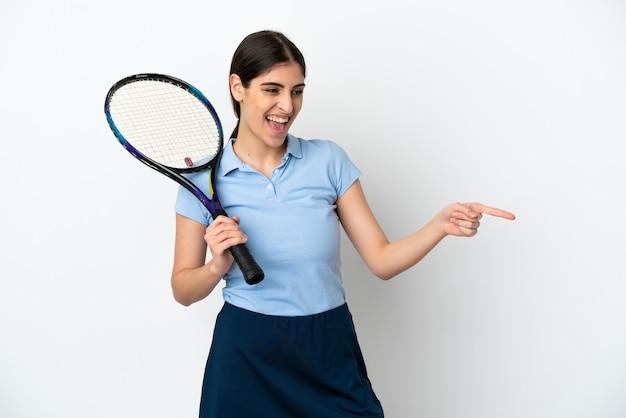 横に指を指し、製品を提示する白い背景で隔離のハンサムな若いテニスプレーヤー白人女性