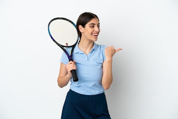 製品を提示する側を指している白い背景で隔離のハンサムな若いテニスプレーヤー白人女性