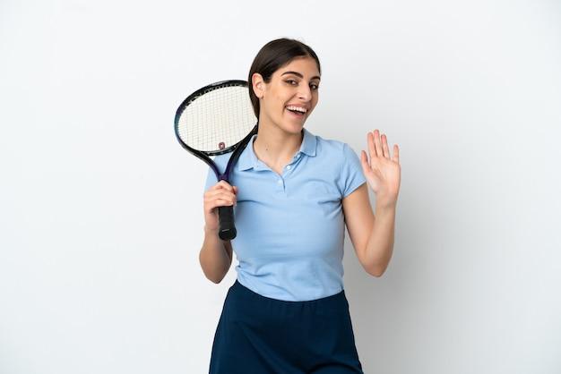 幸せな表情で手で敬礼する白い背景で隔離のハンサムな若いテニスプレーヤー白人女性