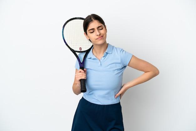 努力したために腰痛に苦しんでいる白い背景で隔離のハンサムな若いテニスプレーヤー白人女性