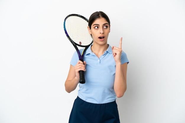 指を上に向けるアイデアを考えて白い背景で隔離のハンサムな若いテニスプレーヤー白人女性