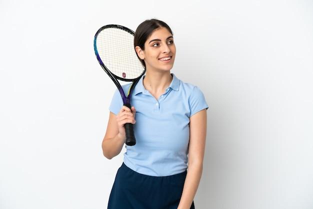 흰색 배경에 격리된 잘생긴 젊은 테니스 선수 백인 여성