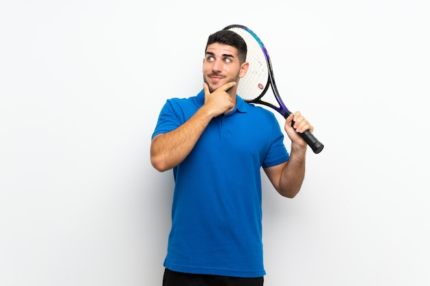 Handsome young tennis player man over isolated white wall thinking an idea