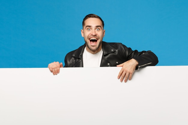Handsome young unshaven man hold big white empty blank billboard for promotional content isolated on blue wall background studio portrait. people sincere emotions lifestyle concept. mock up copy space