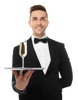白い表面に、シャンパングラスとトレイを保持しているハンサムな若いウェイター