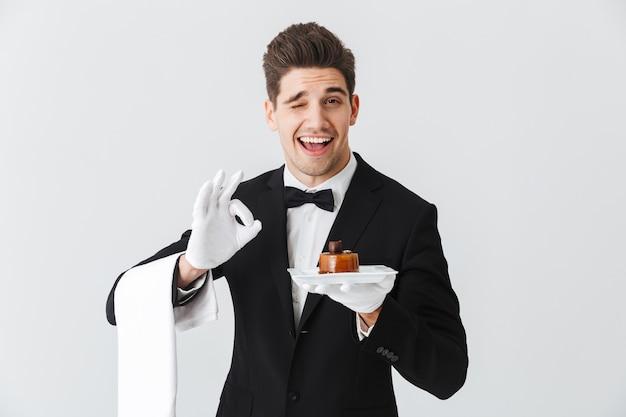 Красивый молодой официант в смокинге с бабочкой, держащей тарелку с тортом, изолированным над белой стеной, хорошо