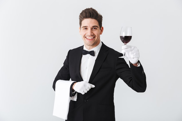 Красивый молодой официант в смокинге с бокалом красного вина, изолированным над серой стеной