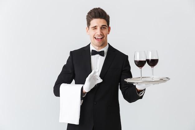 Красивый молодой официант в смокинге представляет поднос с двумя бокалами красного вина, изолированными над серой стеной