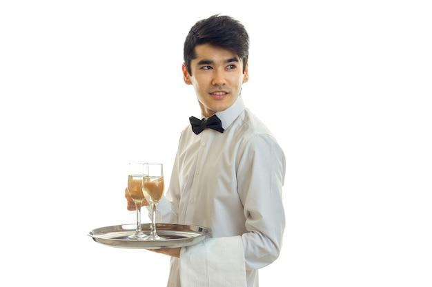 나비 넥타이와 셔츠와 잘 생긴 젊은 웨이터는 멀리 보이고 흰 벽에 고립 된 트레이에 샴페인 잔을 유지