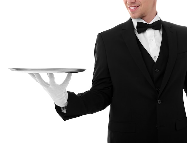 Handsome young waiter with tray on white