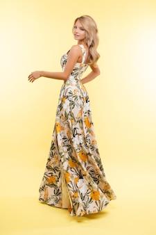 Bella giovane donna in abito lungo posa per la fotocamera, immagine isolata su sfondo giallo