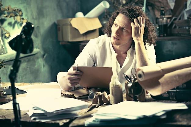 テーブルに座っていると彼のスケッチパッド自宅で何かを書くハンサムな若い作家