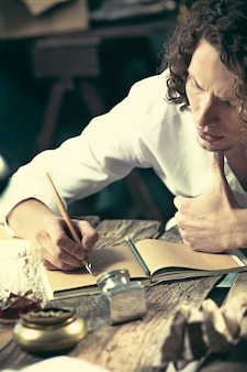 Handsome young writer sitting at the table and writing something in his sketchpad at home