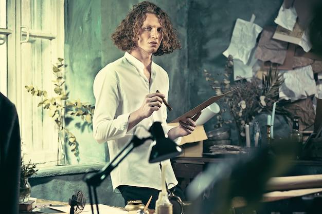 Красивый молодой писатель стоит возле стола и что-то придумывает