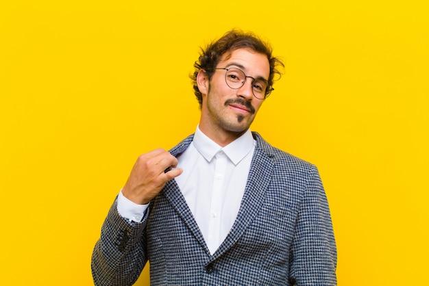 Handsome慢、成功、肯定的で誇りに思って、オレンジ色の壁に対して自己を指している若いハンサムな男