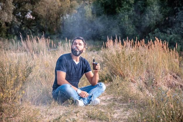 ハンサムマンは屋外でアークを吸う煙を吐き出します。新技術のたばこ。