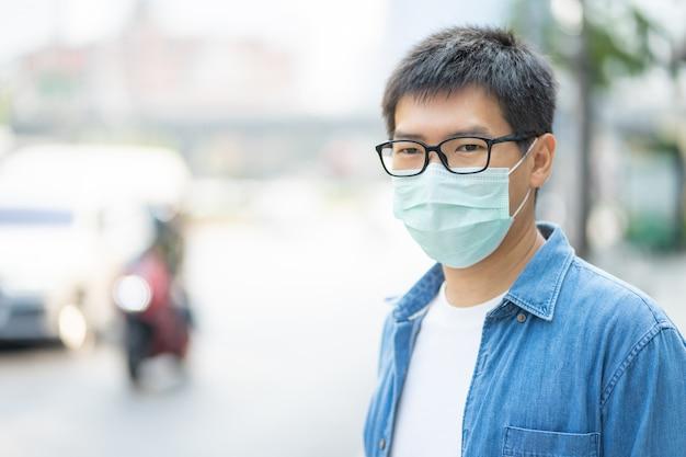 フェイスマスクを着用しているハンサムマンは、フィルターを大気汚染(pm2.5)から保護するか、n95マスクを着用します。守る