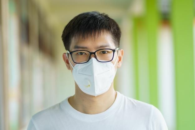 フェイスマスクを着用しているハンサムマンは、フィルターを大気汚染(pm2.5)から保護するか、n95マスクを着用します。