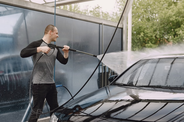 Handsomen man in a black sweater washing his car