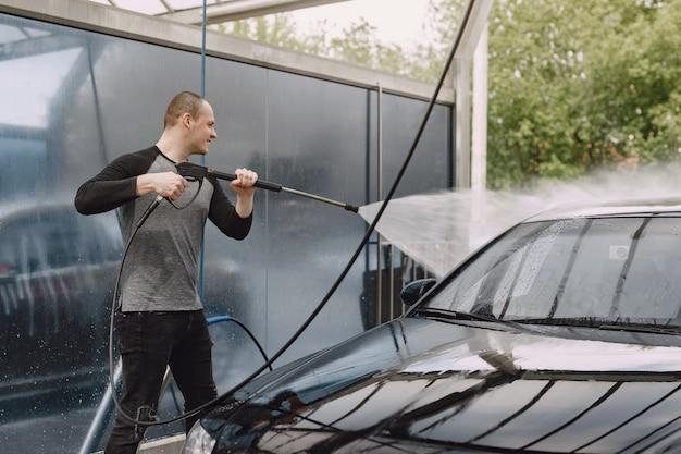 Uomo di handsomen in un maglione nero che lava la sua automobile