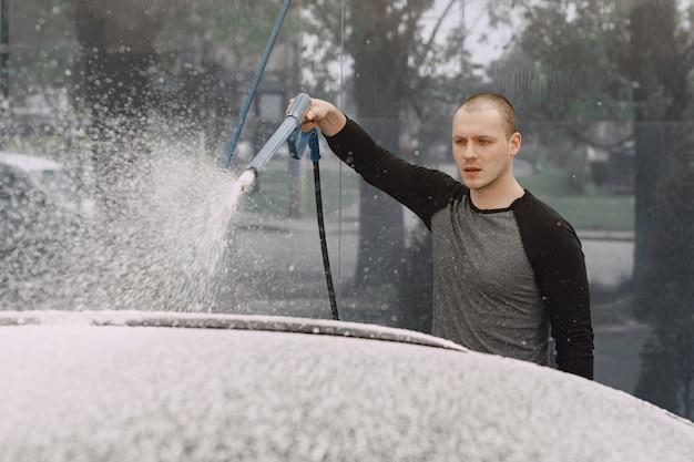 Handsomen человек в черном свитере моет машину