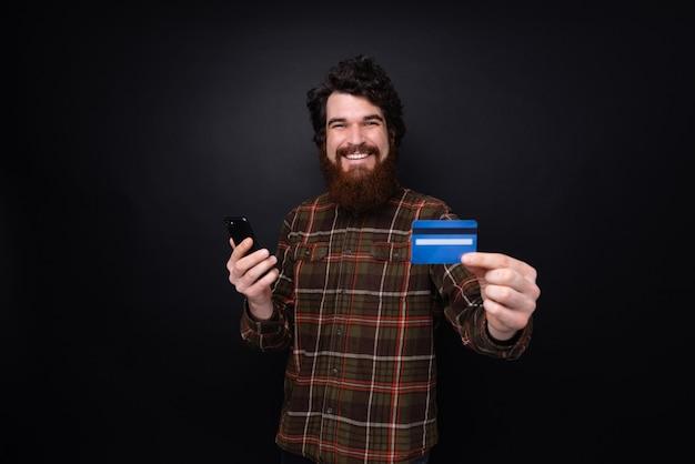 스마트폰을 들고 카메라에 신용 카드를 보여주는 체크 무늬 셔츠에 handsone 수염된 남자