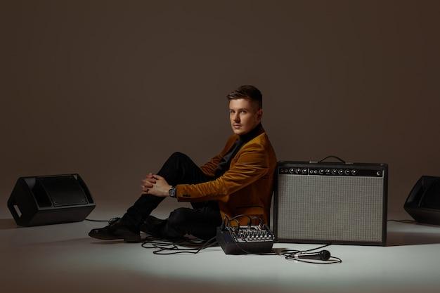 Handsone singer sitting near loudspeakers